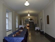 2. kerroksen aula, jossa tarjoilupöytiä ikkunoiden alla toisella sivustalla.