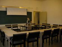 Sali 401, jossa pöydät aseteltu O-mallissa ja istuomet ulkolaidoilla.